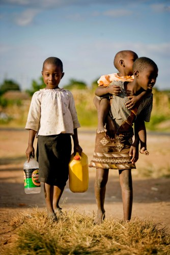 Children carry their water containers as they  walk towards  one of 22 boreholes that the AusAid have helped to fund, in partnership with Unicef in  Budiriro following a cholera outbreak